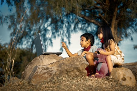two children use laptop outside for remote schooling