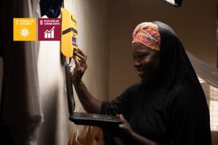 Nainen helppokäyttöisen aurinkoenergialaitteen kanssa