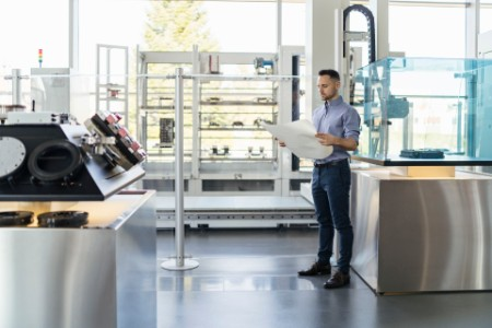 Businessman looking at plan in modern factory