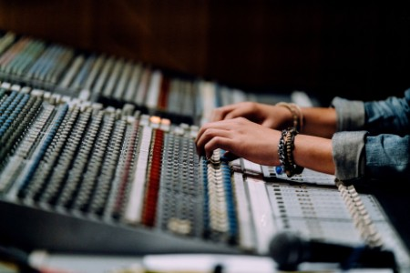 Close up of audio engineers hands on mixer