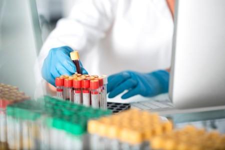 Primer plano de un técnico de laboratorio examinando tubos de ensayo en el laboratorio
