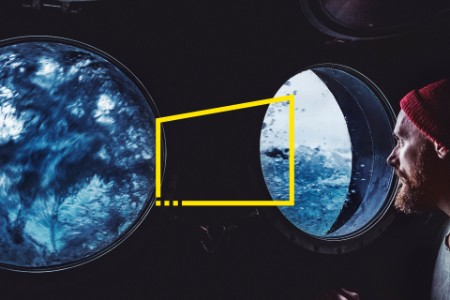 Man at the porthole of a vessel in a rough sea