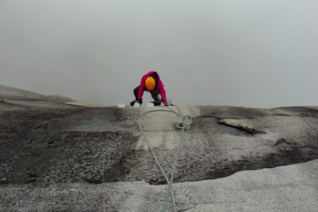 man climing up cliff on rope in fog