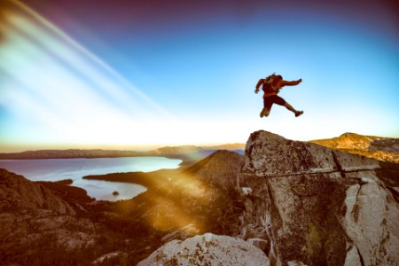 Man jumps and kicks on the summit of mountain overlooking lake tahoe california