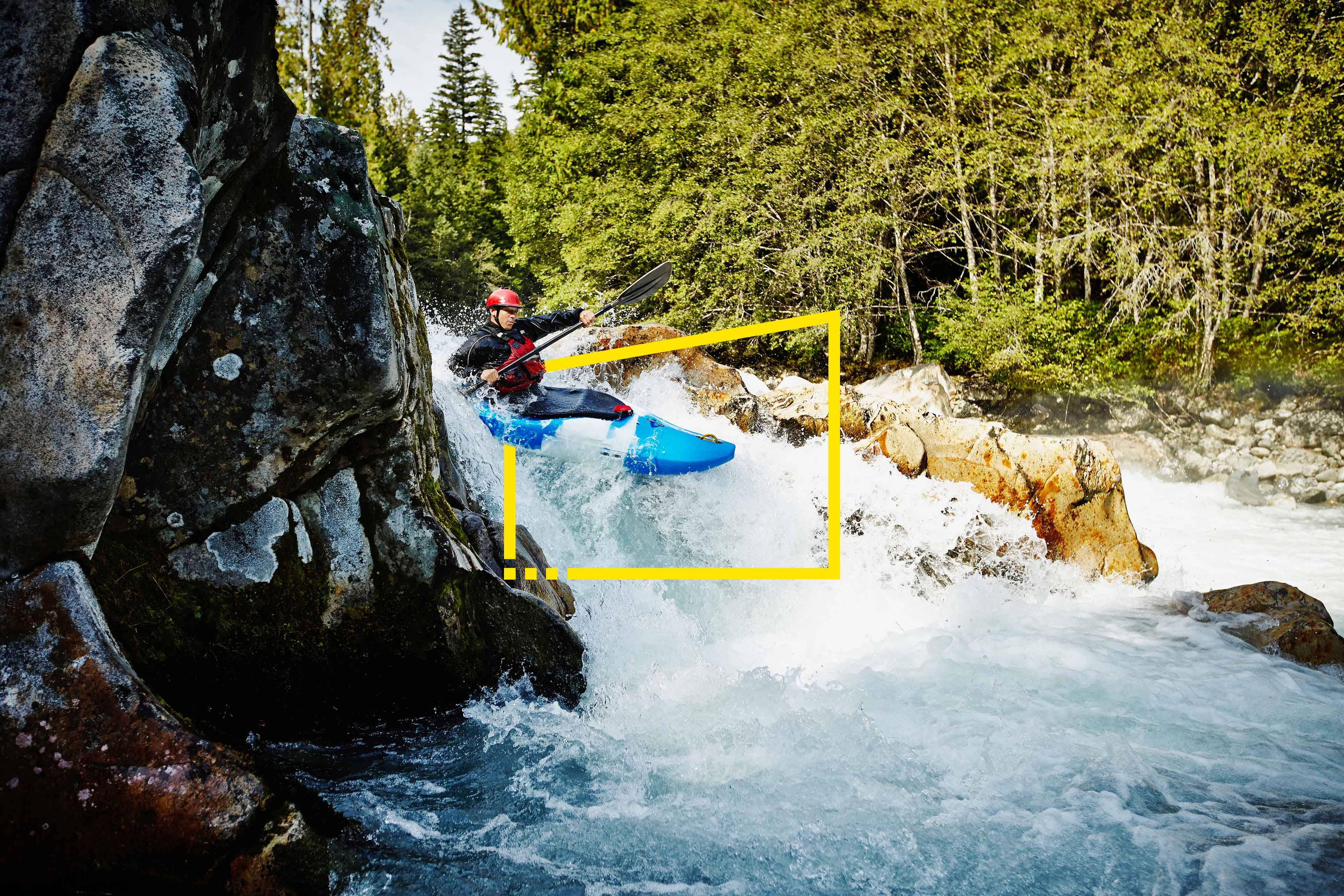Man kayaking between rocks in white water rapids