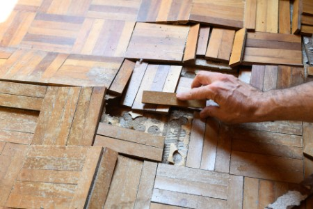 Man hand fixing up a broken wooden floor