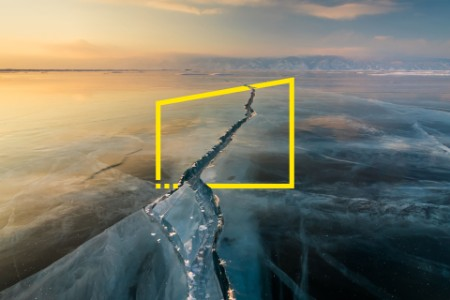 Sunset on the ice with cracks lake Baikal in winter