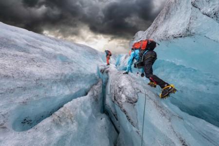 ey-two-men-hiking-up-a-glacier-background