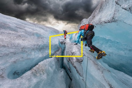 two men hiking up a glacier