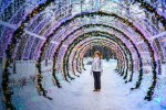Woman is standing under the christmas lights park