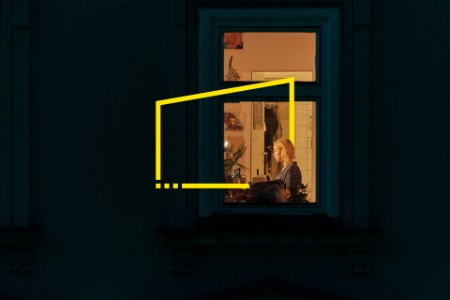 Woman working at home seen throught her window at night