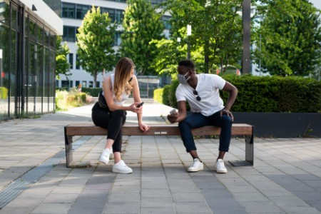 Young man and woman social distancing on a bench using phones