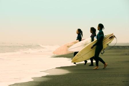 Surfer women walking toward sea with surfboard side view