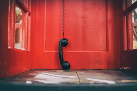 black handset hanging red telephone box