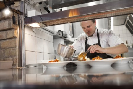 Chef serving food plate kitchen counter restaurant