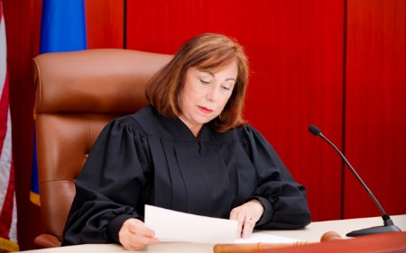 Female judge reading through paperwork in court