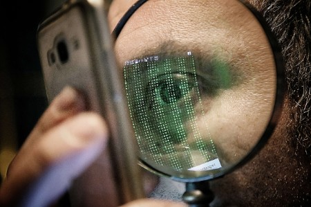 man looks phone magnifying glass
