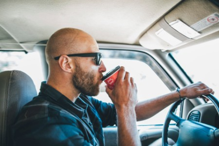 man sunglasses road trip takeaway drink