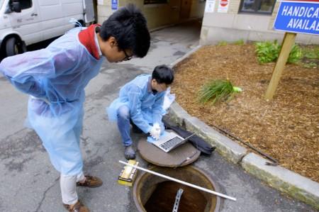 men inspecting sewage drain robot