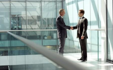 Dois homens apertam as mãos à porta de um edifício