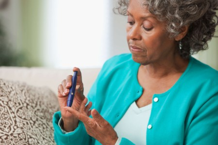 older woman testing blood sugar