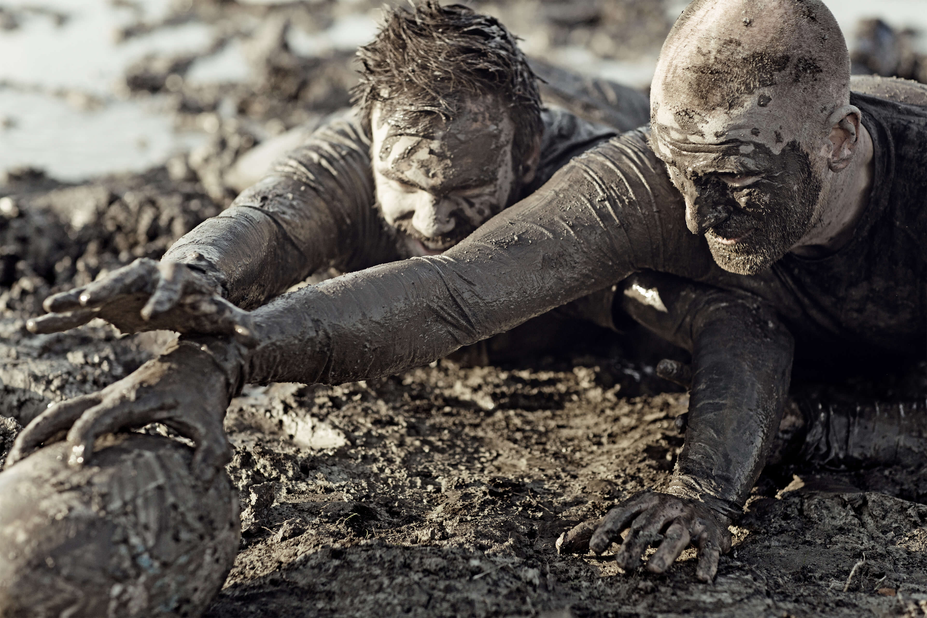 People crawling in the mud and trying to move quickly