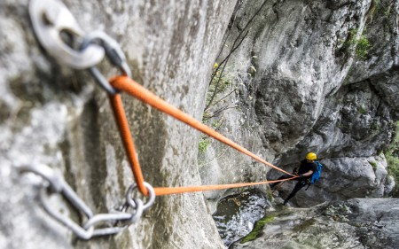 Person climbing rock with three part safety cord