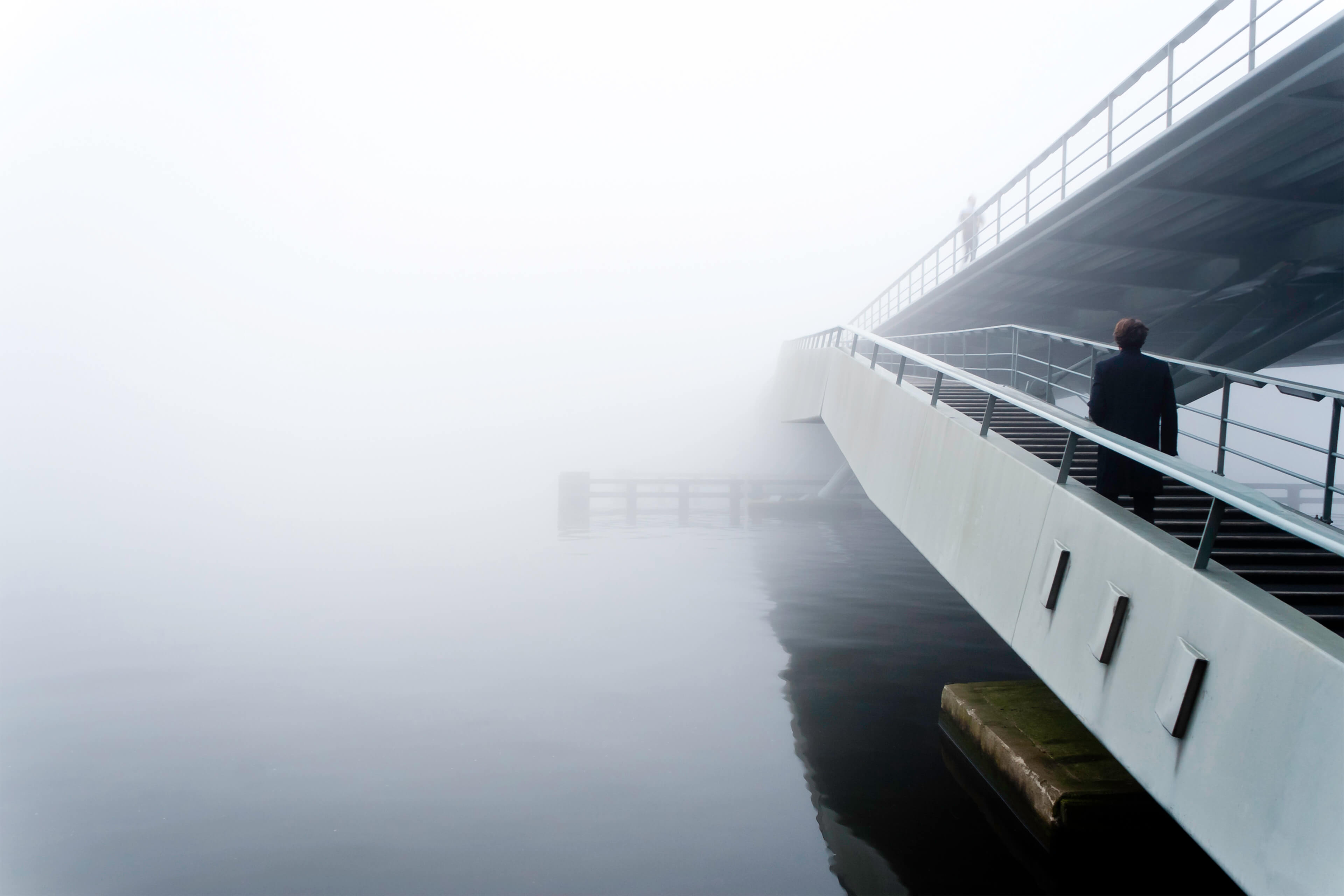 Person walking over a bridge into the fog