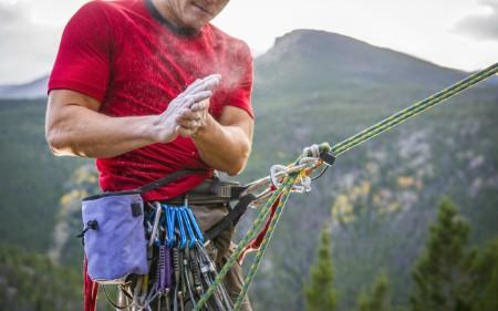 Alpinista a colocar giz nas mãos na preparação para uma escalada