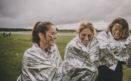 Runners smiling and wearing foil blankets after finishing race