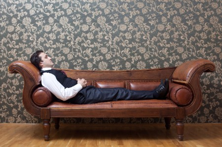 suited man reclining leather couch