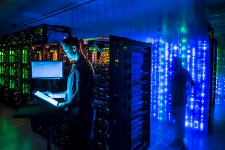 Man using digital tablet in dark server room