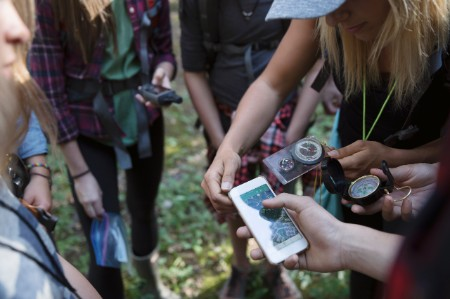 Female teacher and teenage outdoor school students using compass and smart phone gps