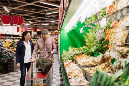 Couple choosing vegetables using phone supermarket