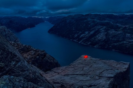 Lone red tent with light on cliff edge.jpg