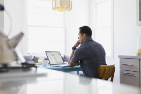 ey-serious-brunette-man-using-laptop-at-kitchen-table