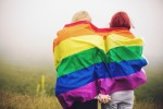Two woman wrapped rainbow flag holding hands