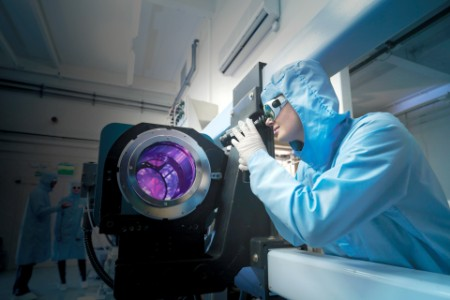Scientist in blue suit working with instrument emitting purple light.