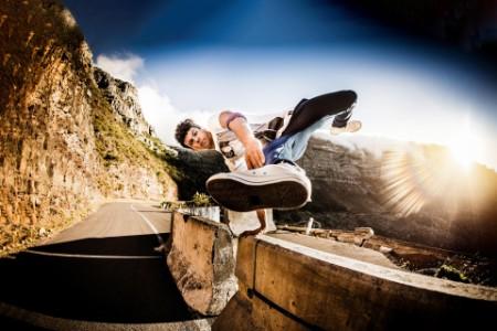 Un adolescent saute par-dessus une barrière routière en béton