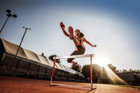Female athlete jumping over hurdle