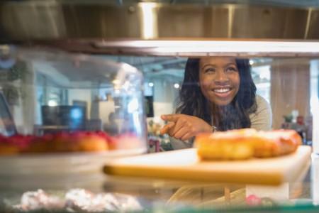Smiling woman choosing dessert bakery display