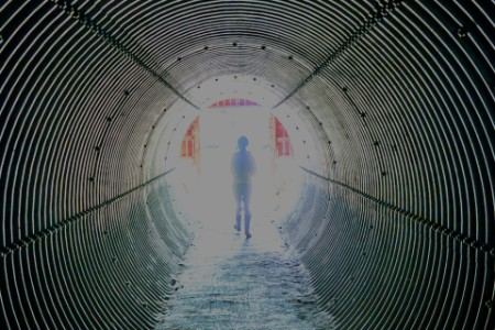 person walking tunnel obscure light