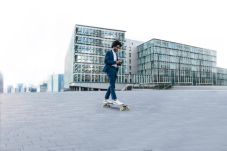 Businessman riding skateboard and using cell-phone