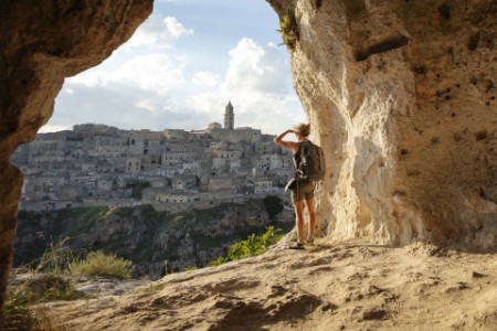 woman looking at view of mountain cave high up