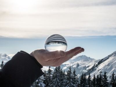 Hand glass ball snowy mountains