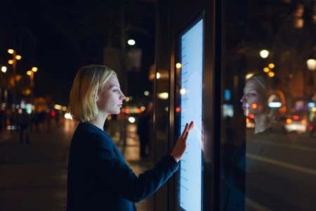 woman in street using touch screen ad display