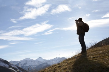 man standing on hill looking out over mountains