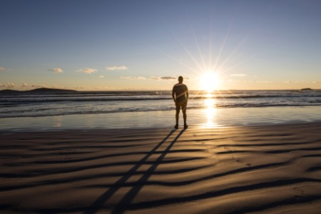 ey-man-standing-on-beach-looking-at-the-sunset