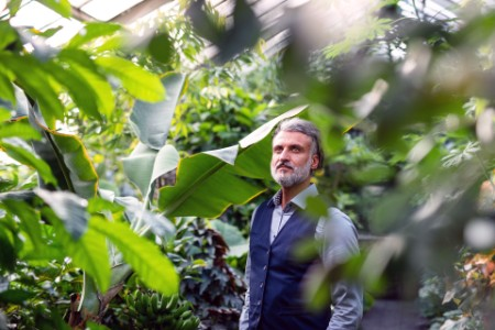 ey-portrait-of-mature-man-relaxing-in-greenhouse
