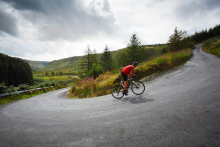 Cyclist climbing hairpin bends up steep road
